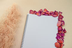 Black notepad. Realistic template notebook. Blank cover design. With dried rose petals and leaf. on cardboard background royalty free stock photo