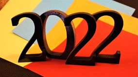 2022 black numbers on colored paper. Red, gold, blue, yellow backdrop outlines the stark contrasting dark numerals of two and zero.  New Year`s celebration stock image