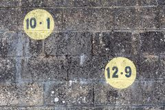 Black numbers in a yellow circle painted on dark brickwork wall in the outdoors Royalty Free Stock Photos