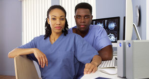 Black nurses in nurses station sitting at computer Royalty Free Stock Images