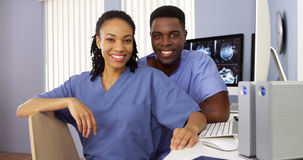 Black nurses in nurses station sitting at computer. Two Black nurses in nurses station sitting at computer Royalty Free Stock Photo