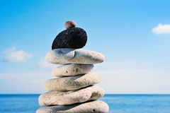Black obelisk. Pile of a sea pebble with a black stone at top Stock Photography