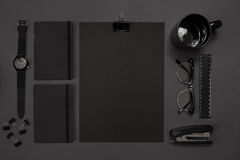 Black objects from the office on a dark gray background. Work and creativity. Top view. Stock Image