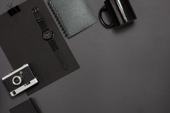 Black objects from the office on a dark gray background. Work and creativity. Top view. Stock Photos