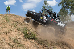 Black off road car leaves a steep hill Stock Image