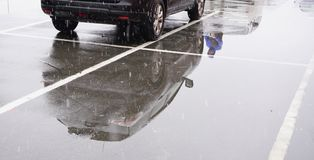Black off-road car stands in parking lot and is reflected in surface of asphalt. Stock Photo