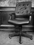 Black Office Chair with Textured Wall Stock Photography