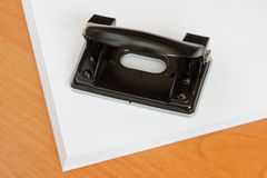 Black office hole punch on a paper stack. Royalty Free Stock Images