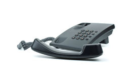 Black office phone with handset in foreground Royalty Free Stock Photos
