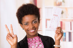 Black office woman tickets. Black office woman holding up ticket and doing a peace sign with other hand concept transport airplane airline bus train traveling Royalty Free Stock Photos