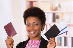 Black office woman tickets and passport. Black office woman holding up tickets and passport document smiling concept transport airplane airline bus train Royalty Free Stock Image