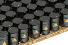 Black oil barrels on pallets. On white background Stock Photography