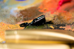 Black oil paint on a palette with blurred colorful background and golden foreground Royalty Free Stock Image