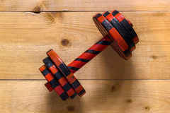 Black-oirange stripped dumbbell on wooden surface. Flat view from top Stock Photography