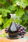 Black old balsamic vinegar in a glass jug with fresh red grapes. On green vineyard background on wooden table, outside royalty free stock images