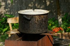 Black old burned pan covered with a white lid on the street. One black old charred pot covered with a white lid on the street stock photos
