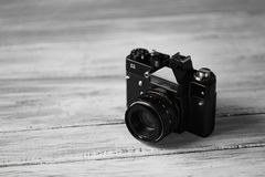 An old vintage black camera, an optical instrument for recording or capturing images on a blurred wooden background. Stock Photos