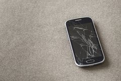 Black old cellphone with cracked screen on light cloth copy space background. Gadget repair and maintenance concept.  stock image
