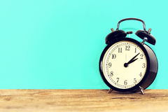 Black old clock, on wooden table. Stock Photo