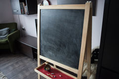 Black old empty chalkboard for copy space with colorful pieces of chalk. Stock Photos