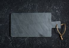 Black old-fashioned stone and slate cutting board on black background Royalty Free Stock Image