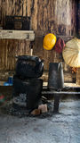 Black old kettle on sitting on small old firewood stove. Black old kettle on sitting on small old firewood stove filled with charcoal inside wooden hut in the Stock Image