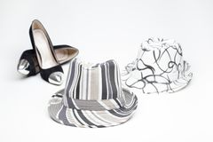 Old ladies shoe on high heels and and a hat. Black old ladies shoe on high heels with a hat on a white background royalty free stock photos