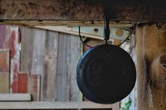 Black and old pan hanging on the wooden balcony. royalty free stock photography