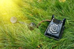 Black old retro telephone in the grass with sunshine Stock Photography