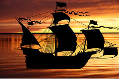 Black old ship sailing vessel on a red Stock Photography
