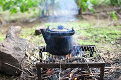 Black old smoked teapot. On the campfire on picnic in wood in the summer stock photography