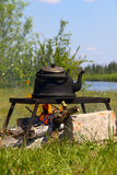 Black old smoked teapot. On the campfire on picnic in wood in the summer Royalty Free Stock Images