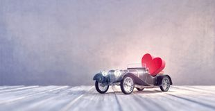 Black Old timer car toy arriving with red heart royalty free stock photos