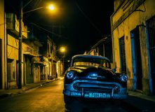 Black oldtimer in a backstreet in santiago de cuba. Black oldtimer standing under the light of street lamps in a backstreet in santiago de cuba Royalty Free Stock Photos