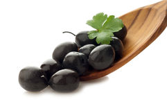 Black  olive  over wood spoon Stock Photo