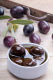 Black olive on a white wodden board Stock Images