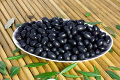 Black olives. Plate of italian black olives over a wood mat Stock Photography
