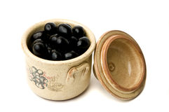 Black olives. In a traditional pot isolated on a white background royalty free stock image