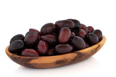 Black Olives. In an olive wood bowl, isolated over white background Royalty Free Stock Photo