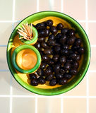 Black Olives. A presentation of black olives in yellow and green ceramic dish Stock Image