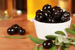 Black Olives. In a bowl with olive oil in the background royalty free stock photography