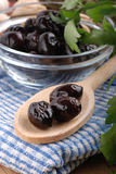 Black olives. On wooden spoon royalty free stock image