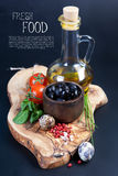 Black olives with bottle of oil on a wooden table Stock Photography