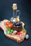 Black olives with bottle of oil on a wooden table Stock Image