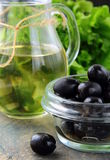 Black olives and a bottle of olive oil. On a wooden table Royalty Free Stock Photography