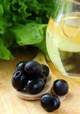 Black olives and a bottle of olive oil. On a wooden table Royalty Free Stock Photos