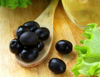 Black olives and a bottle of olive oil. On a wooden table Stock Photography