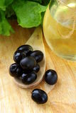 Black olives and a bottle of olive oil. On a wooden table Royalty Free Stock Image