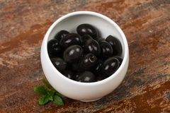 Black olives in the bowl. Black olives heap in the bowl stock photo