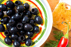 Black olives. In a bowl with hot pepper and toast. Top view stock photo